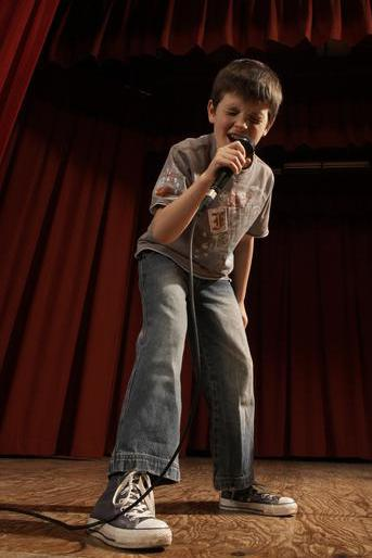 Boy (8-10) performing on stage, singing into microphone, low angle